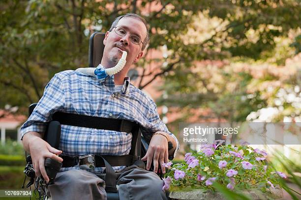 man with duchenne muscular dystrophy sitting in a wheelchair with a breathing ventilator - duchenne muscular dystrophy stock photos and pictures