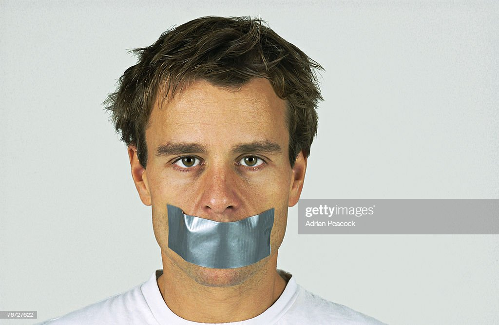 Man with duct tape over mouth : Stock Photo