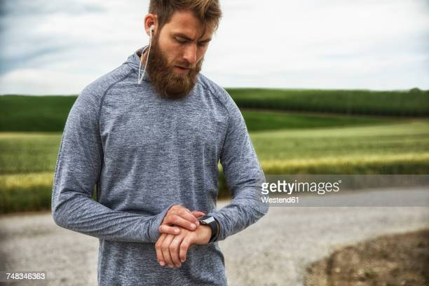 man with earphones using smartwatch, standing outdoors - sportkleidung stock-fotos und bilder