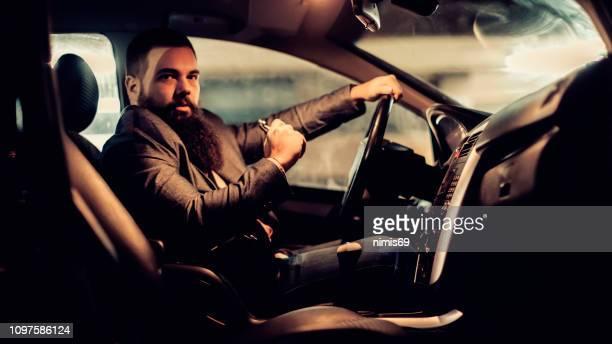 hombre con cigarrillo eléctrico coche privado por la ciudad en la noche - electric car fotografías e imágenes de stock