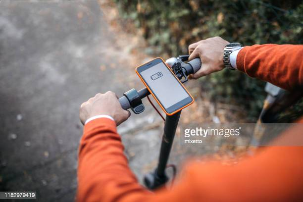 man with electric scooter and mobile phone - low stock pictures, royalty-free photos & images