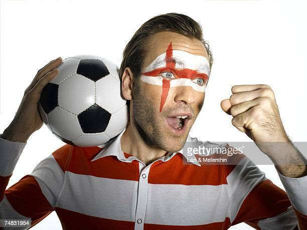 Man with English flag painted on face, shouting, portrait