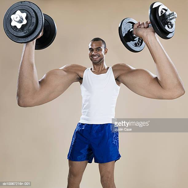 Man with enlarged arms lifting weights, portrait (Digital Composite)