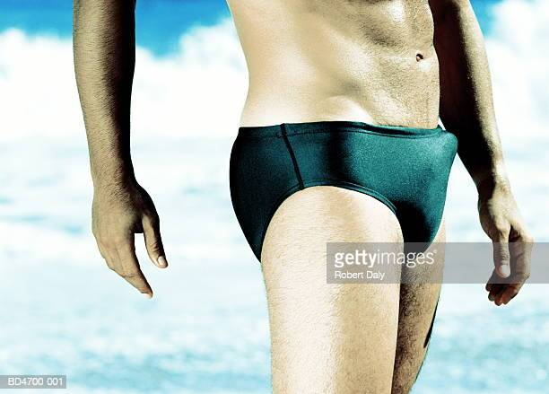 man with erection in swimming trunks, close-up - erectie stockfoto's en -beelden