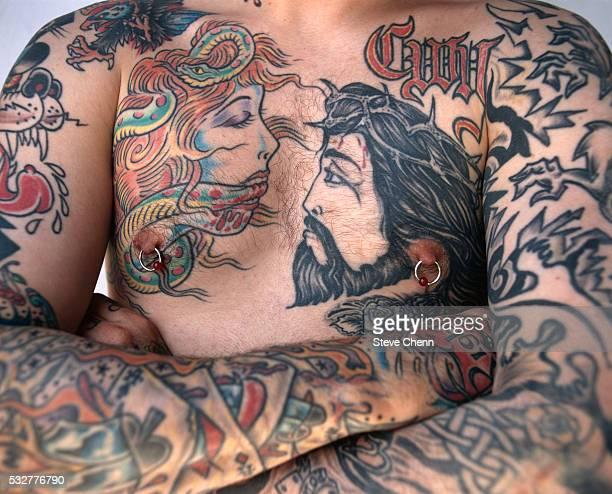 man with eve and jesus tattooed on his chest - tatoeage stockfoto's en -beelden