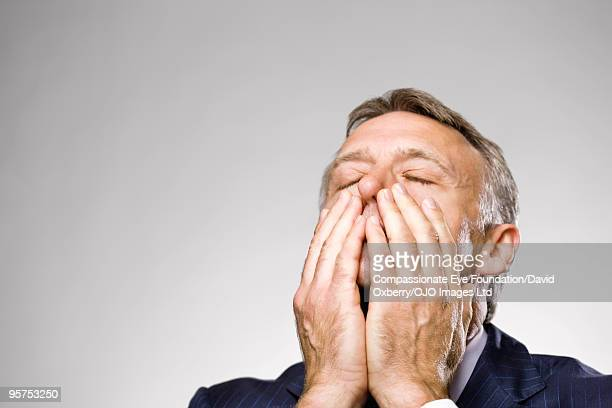 man with eyes closed holding his face - hands covering mouth stock pictures, royalty-free photos & images