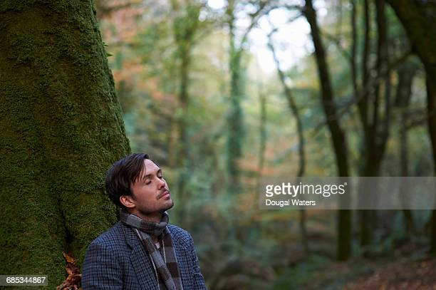 Man with eyes closed in Autumn woodland.
