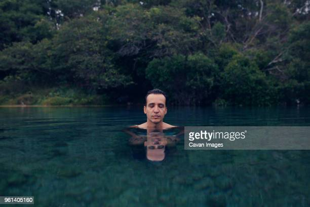 Man with eyes closed in lake