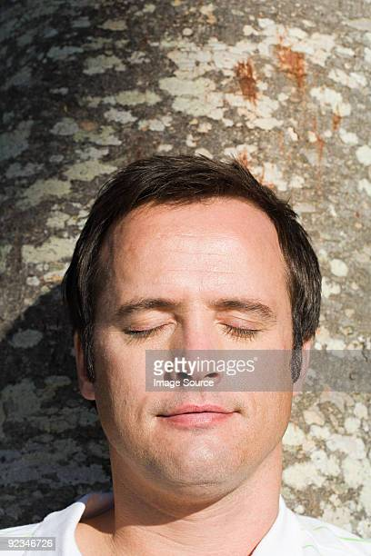 Man with eyes closed resting against tree trunk