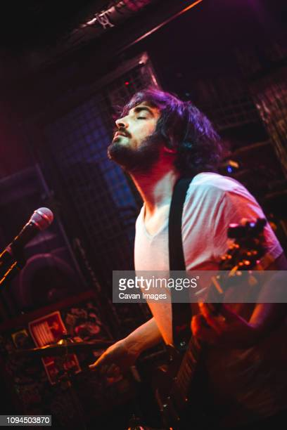 man with eyes closed singing and playing guitar in nightclub - guitarist stock pictures, royalty-free photos & images