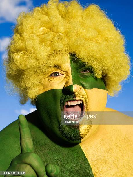 Man with face and body painted green and yellow, portrait