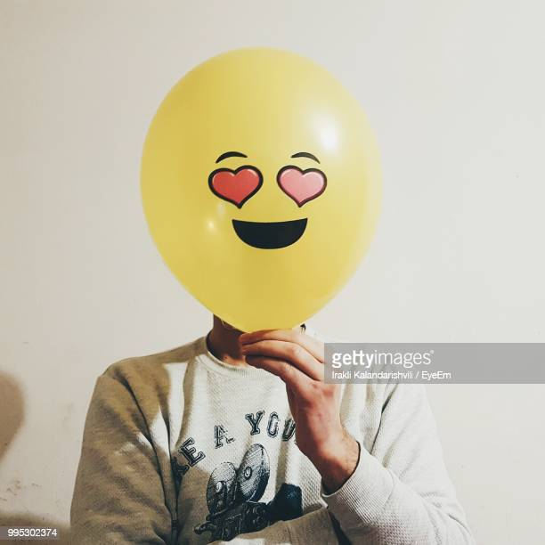 Man With Face Covered By Balloon Against Wall