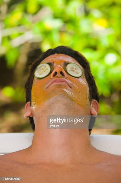 Man with face cream mask and cucumbers in eyes