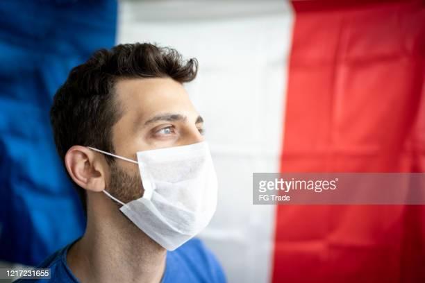mens met gezichtsmasker en franse vlag op achtergrond - france stockfoto's en -beelden