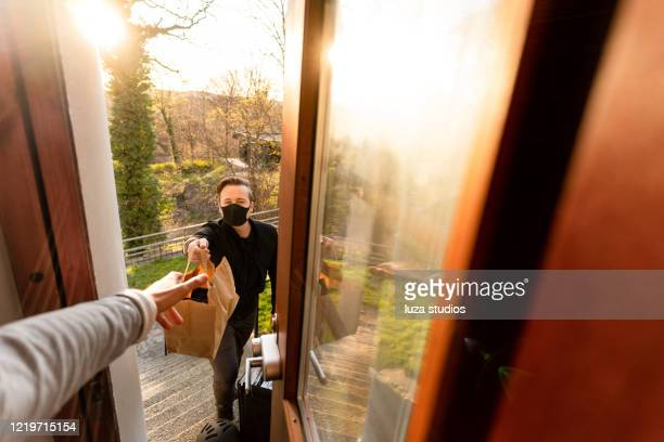 man with face mask delivering food - fast food stock pictures, royalty-free photos & images