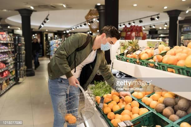 mann mit gesichtsmaske zum schutz vor grippevirus-shopping - grippeschutzmaske stock-fotos und bilder