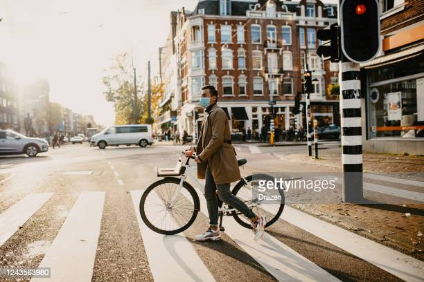 man with face mask pushing bicycle in the city during coronavirus pandemic lockdown - netherlands stock pictures, royalty-free photos & images
