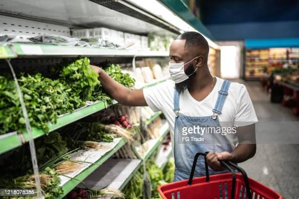 homem com máscara facial andando e fazendo compras em supermercado - ciência e tecnologia - fotografias e filmes do acervo