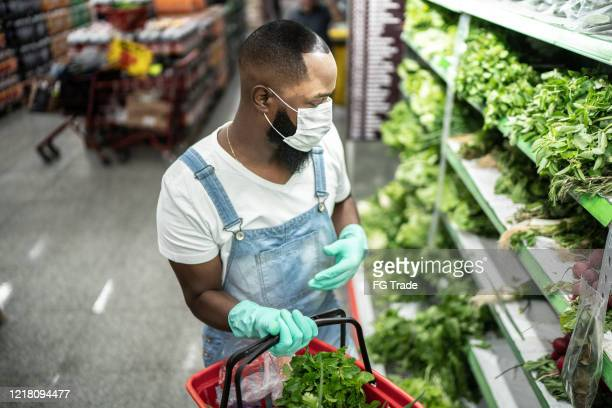 man with face mask walking and shopping in supermarket - black glove stock pictures, royalty-free photos & images