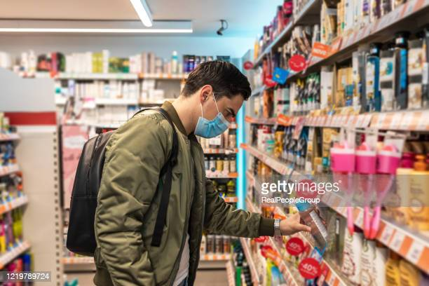 man with face mask walking and shopping in supermarket - panic buying stock pictures, royalty-free photos & images