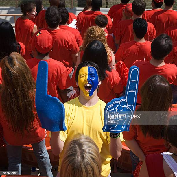 man with face paint cheering - foam finger stock photos and pictures