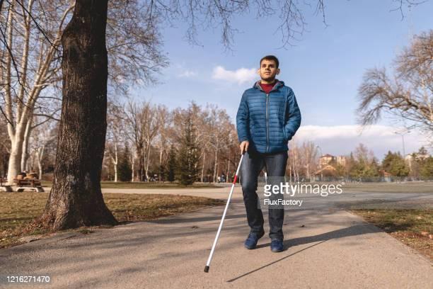 公共の公園で散歩を楽しむ視力の失敗を持つ男 - 白杖 ストックフォトと画像