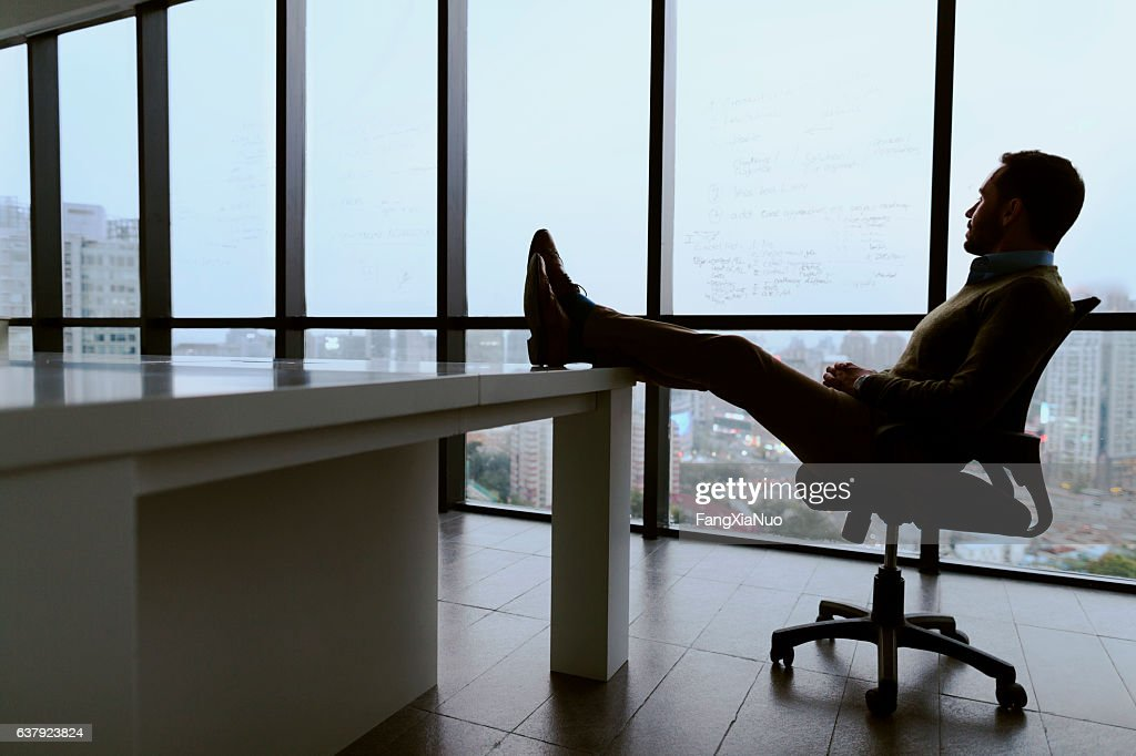 Man with feet propped up on table in meeting room : ストックフォト