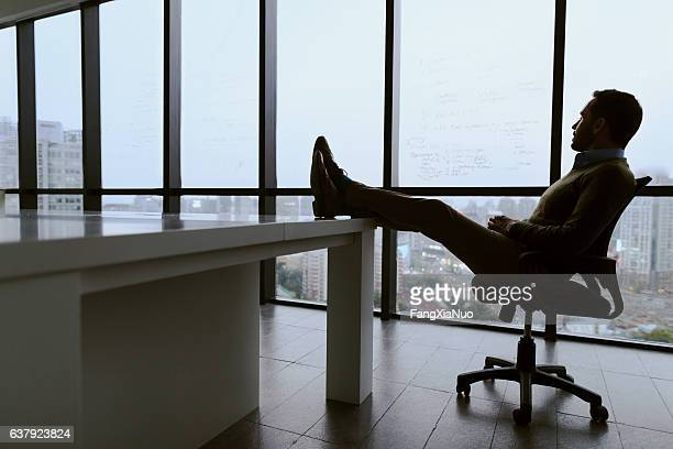 Man with feet propped up on table in meeting room