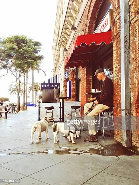 男性、いくつかの犬での屋外のピッツェリアラウンジ