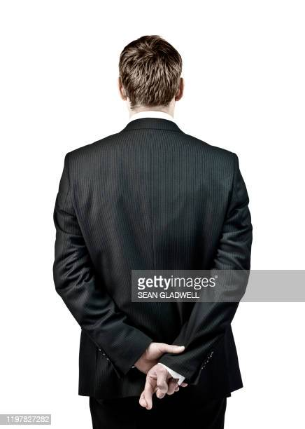 man with fingers crossed behind back - double breasted stock pictures, royalty-free photos & images