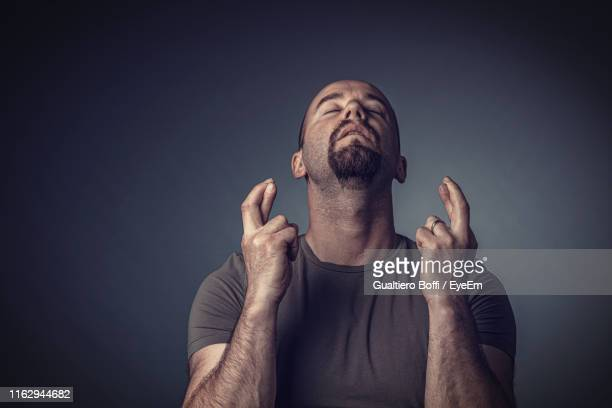 man with fingers crossed standing against gray background - luck stock pictures, royalty-free photos & images