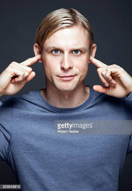 man with fingers in ears - fingers in ears stock pictures, royalty-free photos & images