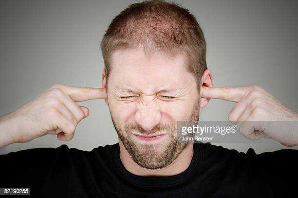 man with fingers in ears