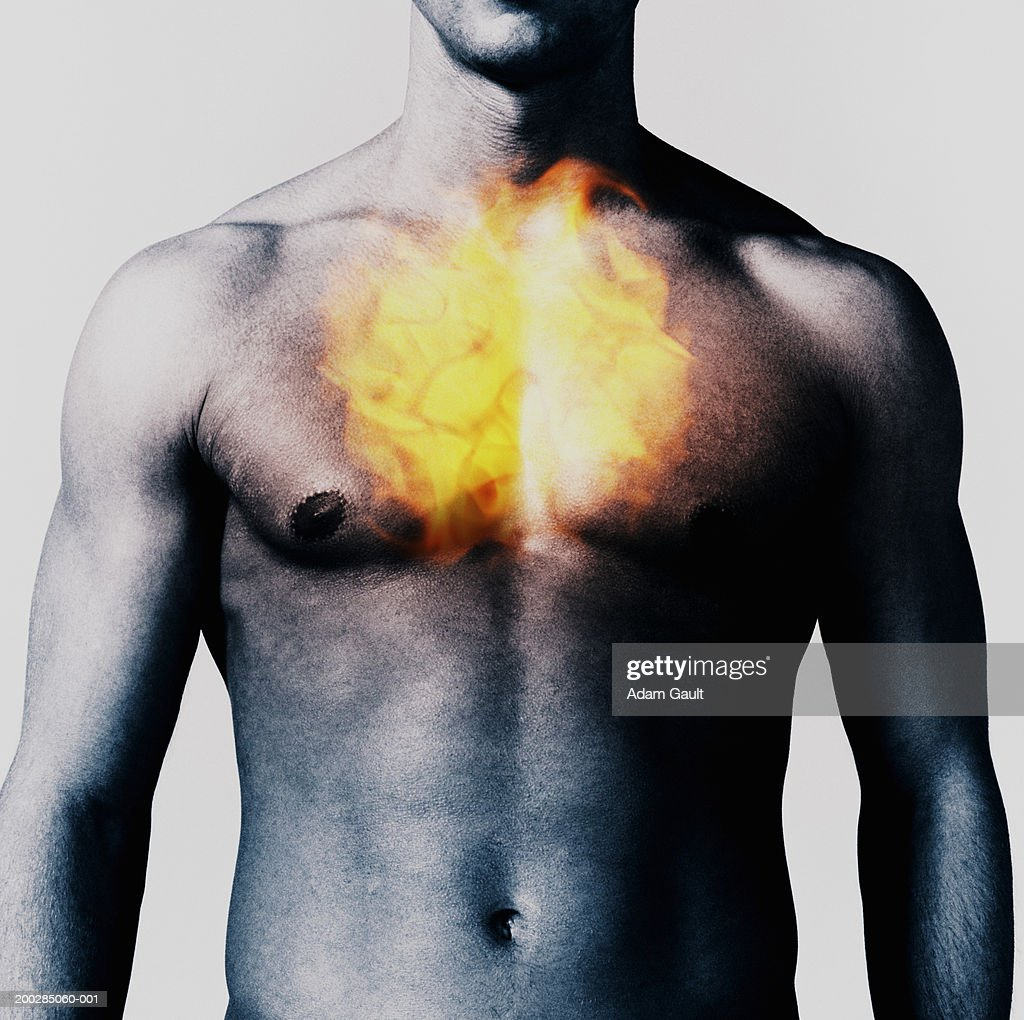 Man with fireball over chest, mid section : Stock Photo