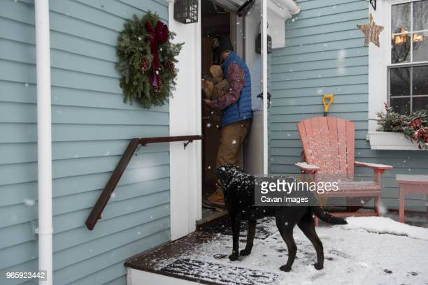 man with firewood entering into house while dog standing at doorway - entering stock pictures, royalty-free photos & images