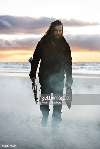 Man with fish and speargun walking on beach