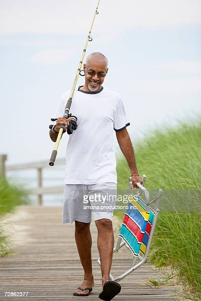 man with fishing rod and folding chair walking on boardwalk - cadeira dobrável - fotografias e filmes do acervo