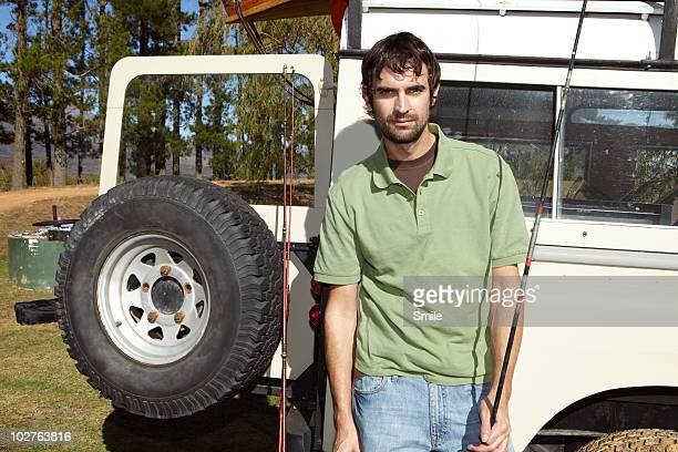 Man with fishing rod leaning against 4x4 vehicle