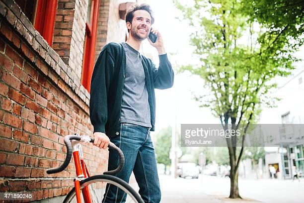 男性、固定ギアバイクとスマートフォン