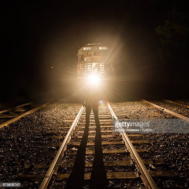 Man With Flaming Torch In Front Of Train Standing At Railroad Track