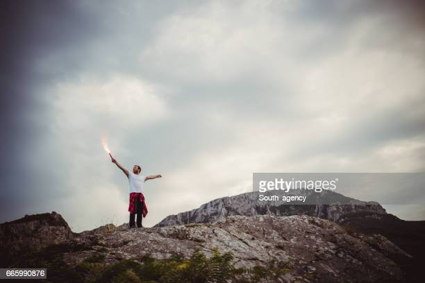 Man with flaming torch on mountain