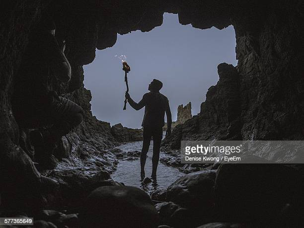 man with flaming torch walking in cave - cave fire stock photos and pictures