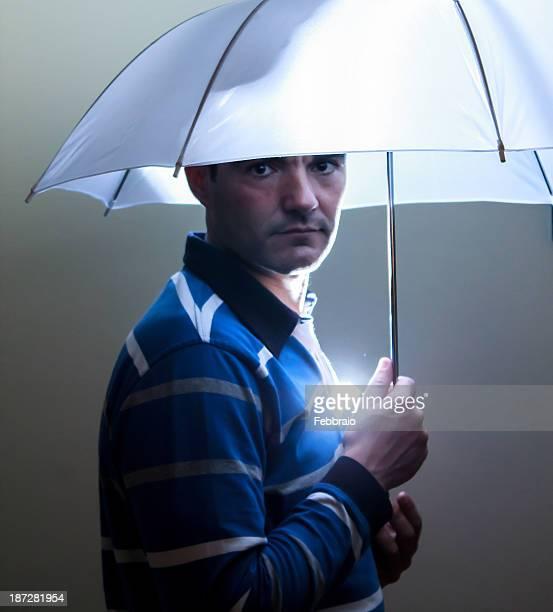 Man with flash illuminating white umbrella