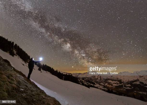 man with flashlight standing against star field on snowcapped mountain - schwyz stock pictures, royalty-free photos & images