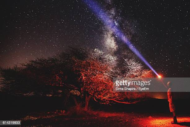 Man With Flashlight Standing On Field Against Star Field At Night