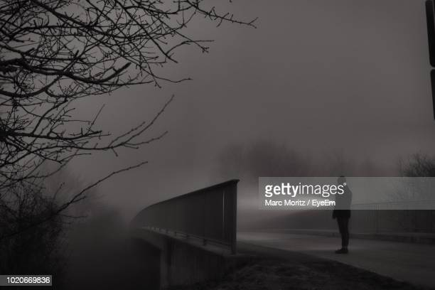man with flashlight standing on road at night - flashlight stock pictures, royalty-free photos & images