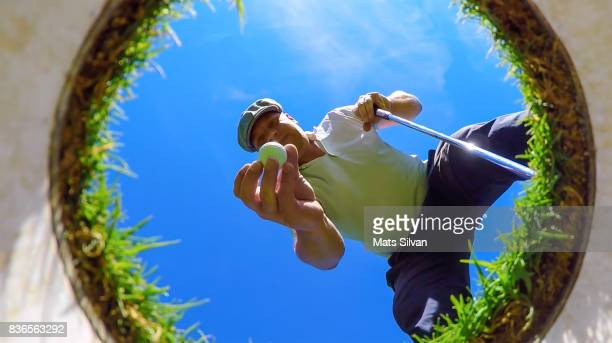 Man with Flat Cap Picking Up his Golf Ball From the Hole