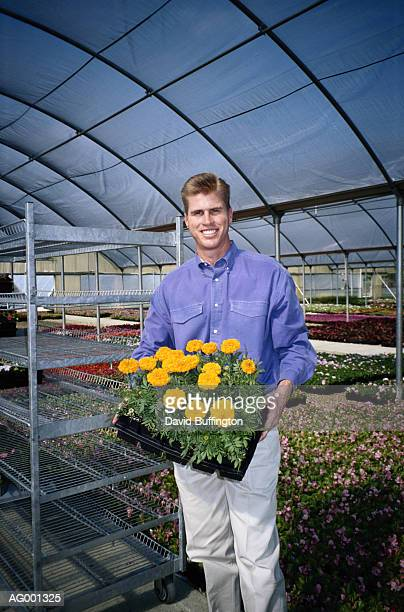 Man with Flowers in Greenhouse