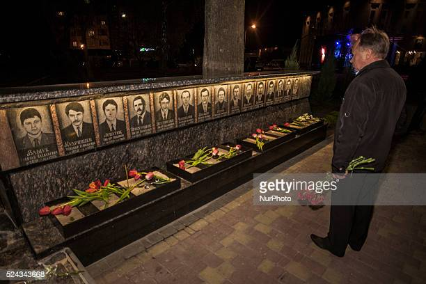 Man with flowers looks the memorial to Chernobyl firefighters in Slavutych Ukraine on April 26 during the ceremony of the 30th anniversary of the...