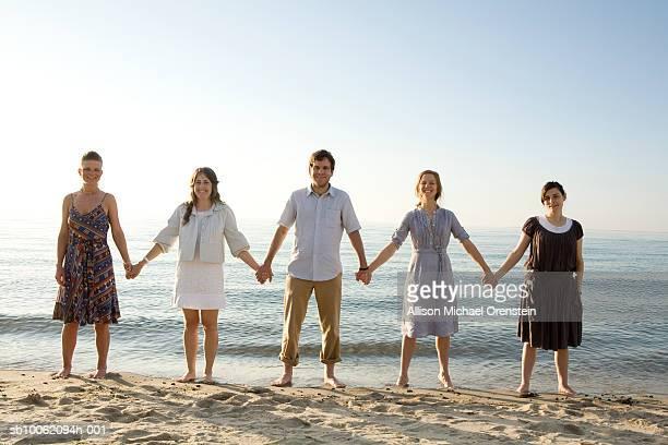 man with four women holding hands on beach, portrait - menschenreihe stock-fotos und bilder